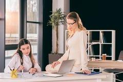 Кавказские коммерсантки в formalwear говоря пока работающ на современном офисе Стоковые Фотографии RF