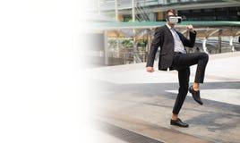Кавказские костюм черноты носки бизнесмена и шлемофон VR и бой виртуальной реальности пинком к воздуху Стоковые Фото