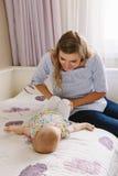 Кавказские мать и младенец совместно на кровати в спальне делая йогу тренировок физического здоровья совместно Стоковое фото RF