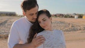 Кавказские молодой человек и женщина прижимаются на пляже видеоматериал