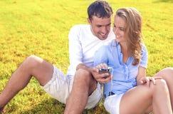 Кавказские пары сидя совместно на траве Outdoors с приятелем Стоковое фото RF