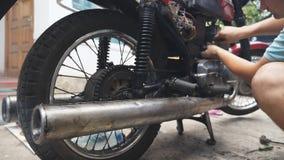 Кавказский автоматический механик ремонтирует его старый мотоцикл внешний Поднимающее вверх замедленного движения близкое акции видеоматериалы