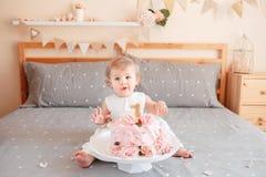 Кавказский белокурый ребёнок в белом платье празднуя ее первый день рождения Стоковые Изображения RF