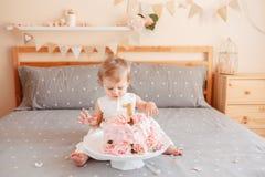 Кавказский белокурый ребёнок в белом платье празднуя ее первый день рождения Стоковые Фотографии RF