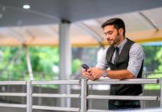 Кавказский белый взгляд бизнесмена на его мобильном телефоне и стойка на пути прогулки поезда неба, также выразили грустную эмоци стоковое фото rf