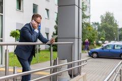 Кавказский бизнесмен вне офиса используя мобильный телефон и tabl Стоковое Изображение RF