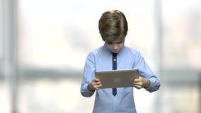 Кавказский мальчик играя игру на планшете ПК видеоматериал