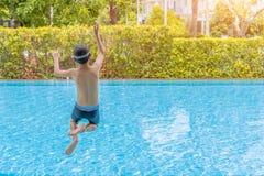 Кавказский мальчик имея потеху скача в бассейн Счастливый ребенк мальчика скача в бассейн стоковое фото