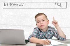 Кавказский мальчик школьного возраста в рубашке шотландки на светлой предпосылке показывает окно с адресом места стоковая фотография rf
