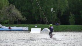 Кавказский молодой человек делая фокусы на wakeboard в озере города