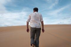 Кавказский молодой человек идя прямо на его путь на песочной пустыне стоковое фото rf