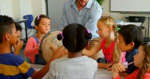 Кавказский мужской учитель уча его детям о глобусе в классе 4k сток-видео