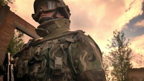 Кавказский настойчивый офицер идя спокойно через получившееся отказ кирпичное здание и держа автоматическое оружие, пасмурный зат иллюстрация штока