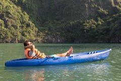 Кавказский путешественник ослабляя в голубом каяке вниз со спокойных вод стоковые фотографии rf