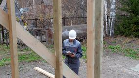 Кавказский работник перед домом Проверка архитектора или построителя планирует в половинном построенном доме рамки тимберса Постр видеоматериал