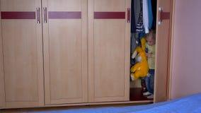 Кавказский ребенок с другом плюша зайчика прячет в шкафе и близкой двери сток-видео