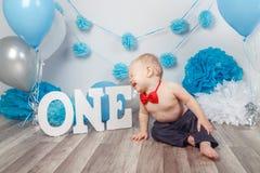 Кавказский ребёнок в темных брюках и голубой бабочке празднуя его первый день рождения с письмами одним и воздушными шарами Стоковое Фото