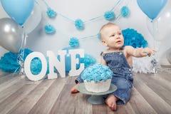 Кавказский ребёнок в темных брюках и голубой бабочке празднуя его первый день рождения с письмами одним и воздушными шарами Стоковое фото RF