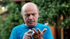 Кавказский старший человек рассчитывать пальцы пашет 5 стоя на предпосылке зеленого сада акции видеоматериалы