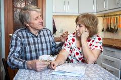 Кавказский супруг пожилых людей успокаивает его жену пока подсчитывающ деньги для общинных оплат стоковые фотографии rf