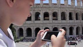 Кавказский турист мальчика отправляя СМС на красивом виде европейского древнего города с передвижным умным телефоном акции видеоматериалы