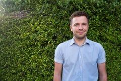 Кавказский человек в голубой рубашке стоя около стены зеленой травы Он усмехающся и чувствующ уверенно Стоковые Фотографии RF