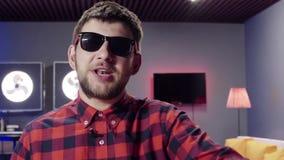 Кавказский человек говорит и динамически хлопает в комнате с загоренн акции видеоматериалы