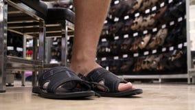 Кавказский человек пробуя на ботинках пальца ноги нового лета открытых в магазине во время покупок обуви сток-видео
