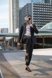 Кавказский шлемофон VR и бой виртуальной реальности носки бизнесмена пинком к воздуху Стоковое Фото