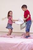2 кавказских дет имея смешное сражение подушки на кровати внутри помещения Стоковая Фотография