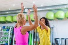 2 кавказских женщины давая максимум 5 после тренировки в спортзале Стоковая Фотография RF