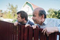 2 кавказских люд тщательно наблюдая над загородкой Стоковая Фотография