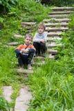 2 кавказских мальчика сидя на каменной лестнице outdoors летом стоковые фото