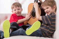 2 кавказских мальчика играя с акустической гитарой Стоковое Изображение