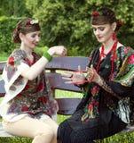 2 кавказских slavonic женщины сидя на стенде Стоковые Фотографии RF