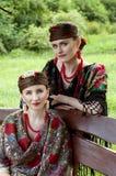 2 кавказских slavonic женщины сидя на стенде Стоковое Фото