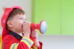 Кавказское платье ребенк мальчика до пожарного и диктора пользы на крене pl Стоковое Изображение