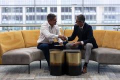 Кавказцы руководителей бизнеса тряся руку пока сидящ на софе стоковые фотографии rf