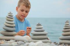 каек мальчика пляжа штабелирует камень Стоковые Изображения