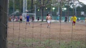 Каждый парк вечера публично имеет людей разнообразия играя футбол совместно на футбольном поле После взгляда цели чистого сток-видео