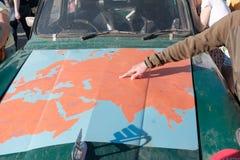 Казахстан, Kostanay, 19-06-19, карта Евразии на клобуке старого автомобиля Рука парня показывает путь движения  стоковое изображение rf