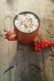 Какао или чашка кофе с вкусными зефирами, ветвь ели с красными ягодами дерева рябины Натюрморт на старое деревенском Стоковые Изображения