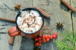Какао или чашка кофе с вкусными зефирами, ветвь ели с красными ягодами дерева рябины Натюрморт на старое деревенском Стоковая Фотография RF