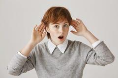 Какие неимоверные новости, делают кто-то еще знать ее Портрет заинтересованной сотрясенной женщины redhead держа руки приближает  стоковые изображения