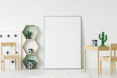Кактус на деревянном столе рядом с белым пустым плакатом с модель-макетом внутри Стоковое Изображение RF