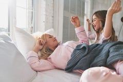 Как раз одна больше минуты в кровати? Милая маленькая девочка просыпая вверх ее щеголь стоковые фото