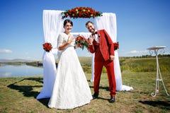 Как раз пожененная положительная выставка жениха и невеста звенит после свадебной церемонии Стоковые Фотографии RF
