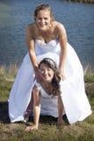 Как раз пожененная счастливая лесбосская пара в белом платье имеет потеху около sm Стоковые Изображения RF
