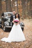 Как раз пожененные пары в роскошном ретро автомобиле на их день свадьбы Стоковая Фотография RF