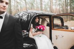 Как раз пожененные пары в роскошном ретро автомобиле на их день свадьбы Стоковые Фотографии RF
